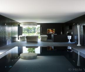 Exclusief betonnen binnenzwembad bekleed met zwarte mozaïek aangelegd door West-Pool zwembadbouwer West-Vlaanderen