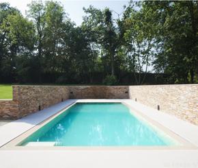 Betonnen zwembad bekleed met natuursteen tegels, Hugelier zwembadbouwer West-Vlaanderen