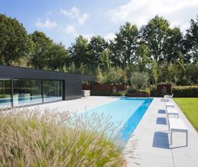 Betonnen zwembad bekleed met witte mozaïek, skimmerzwembad aangelegd door Bob Monteyne