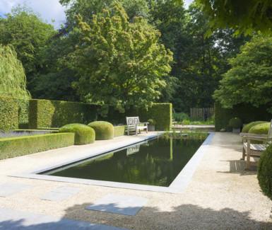 Zwemvijver in tuin met vormsnoei aangelegd door Dhaenens
