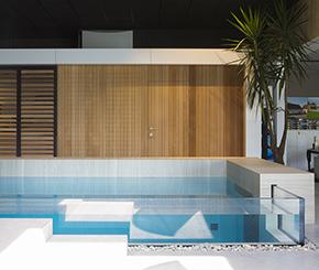 Design binnenzwembad in beton met glazen wand, hoogwaardige afwerkingsmaterialen en zwevende trap