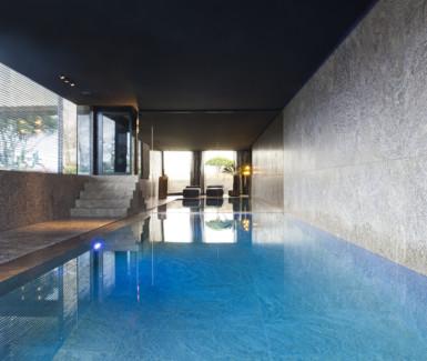 luxe zwembad bekleed met natuursteen, aangelegd door West-Pool zwembadbouwer uit Ingelmunster
