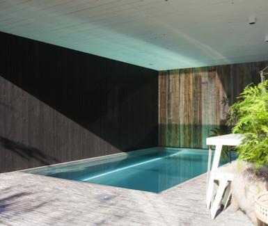 inox binnenzwembad aangelegd in poolhouse uit barnwood door Nouv'eau