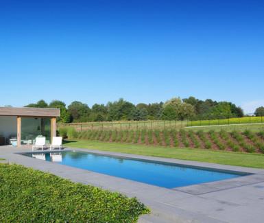 inox buitenzwembad aangelegd door Van Eeckhoudt zwembaden naast poolhouse met sliding doors