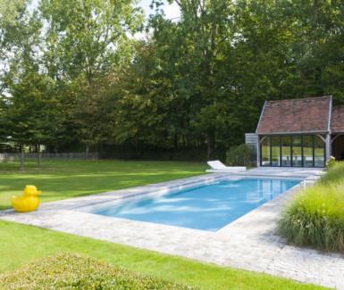 luxueus buitenzwembad bekleed met keramische tegels en glasmozaiek aangelegd door DcPools, demooistezwembaden.be