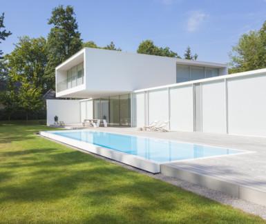 indrukwekkende infinty pool aangelegd door My Pool by Hugelier beschikt over een enorme plage en past perfect bij de minimalistische architectuur van de woning