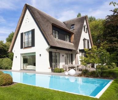 Luxe overloopzwembad bekleed met witte mozaïek en zwevende trap in kleine kusttuin