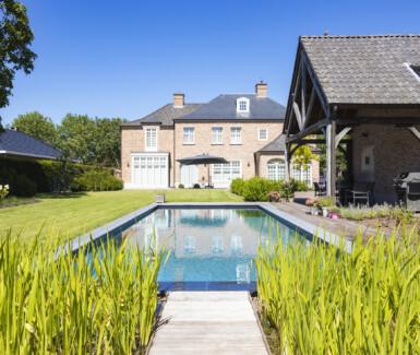 Dit exclusieve biologisch zwembad werd aangelegd door Aqua-Art. Het werd bekleed met een liner en is voorzien van een plage met aansluitende hoektrap