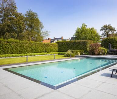 gerenoveerd skimmerzwembad met zitgedeelte over de hele lengte van het zwembad aangelegd door H2eau systems