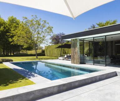 inox skimmer zwembad aangelegd door Nouv'eau naast prachtige houten poolhouse