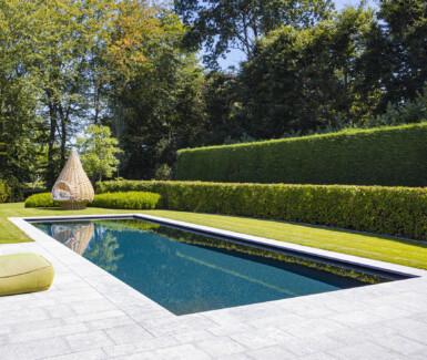 luxueus onderloop zwembad aangelegd door Quality Pool met afgeronde hoektrap, luxe zwembaden