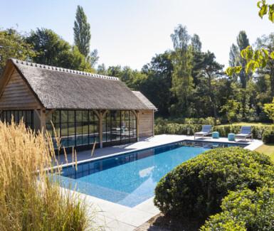 Prachtig onderloop zwembad, aangelegd door Quality Pool, bekleed met blauwe mozaïek in verschillende nuances.