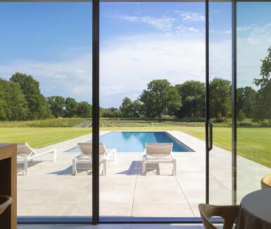 uitgestrekt overloopzwembad  voorzien van jetstream loopt naadloos over in het omliggende landschap. Pool with a view by Swimtec
