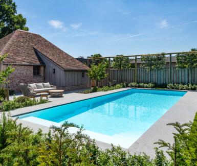 wit polypropyleen zwembad aangelegd door aquapura naast landelijke poolhouse