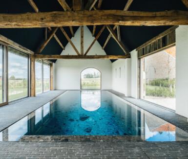 luxe binnenzwembad bekleed met natuursteen aangelegd door Biopool